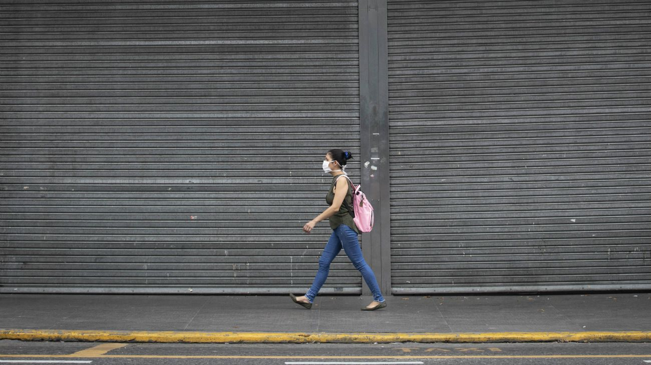 Una mujer porta una mascarilla mientras camina frente a un centro comercial cerrado durante la cuarentena obligatoria decretada por el gobierno, en la ciudad de Buenos Aires