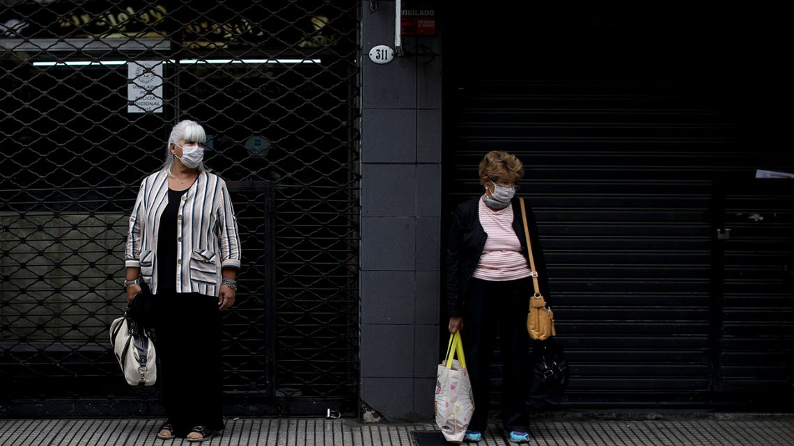 Women wearing face masks to protect against the novel coronavirus wait for a bus in Buenos Aires, Wednesday, April 1, 2020.
