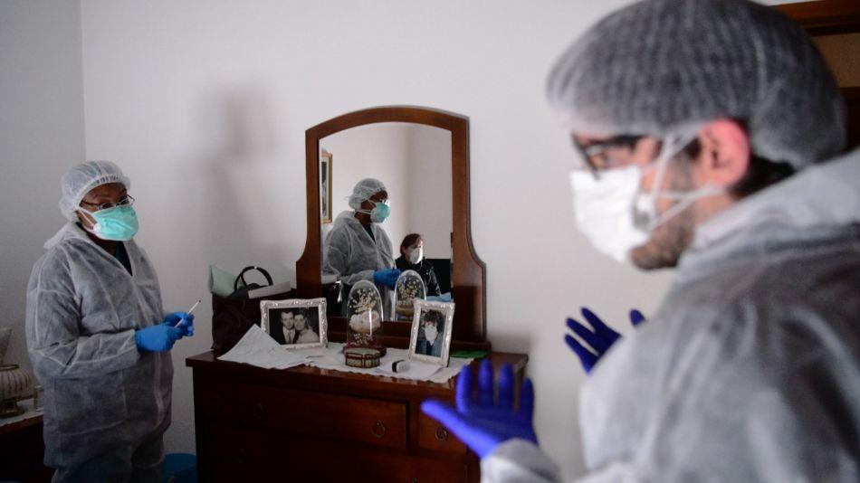 Trabajadores de la salud visitan en Bérgamo a pacientes infectados o con síntomas de Covid-19.