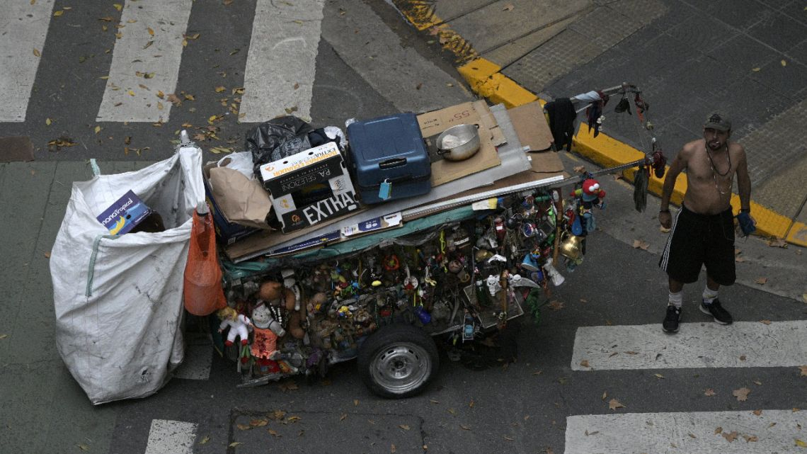 "A homeless man stands next to his cart, which is decorated with things found in the garbage, in Buenos Aires, on April 1, 2020, during a ""preventative and compulsory"" lockdown due to the new coronavirus pandemic."