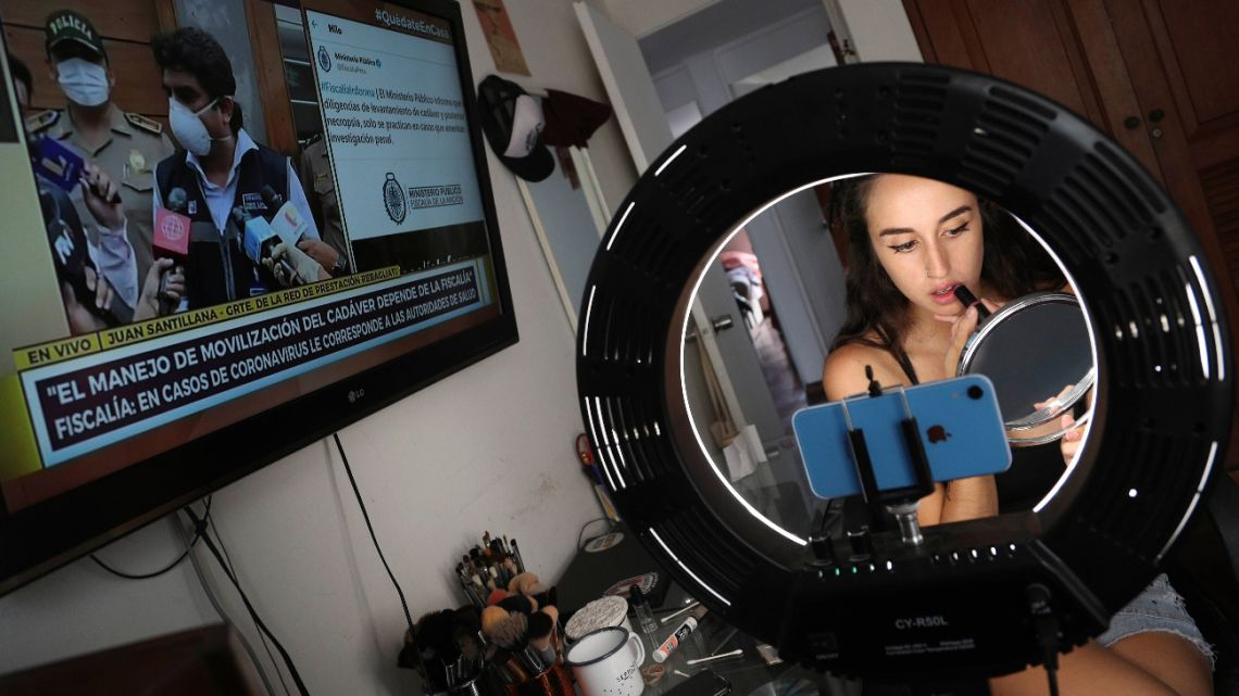 In this March 20, 2020 photo, make-up artist Nadia Muñoz applies lipstick while listening to the television news about the first person in Peru who died of Coronavirus in an upper-middle-class neighborhood of Lima, Peru.