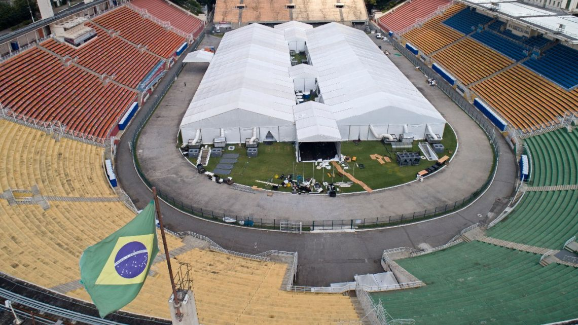Workers set up a temporary field hospital to treat patients who have COVID-19 inside Pacaembu stadium in São Paulo, Brazil, Monday, March 30, 2020.