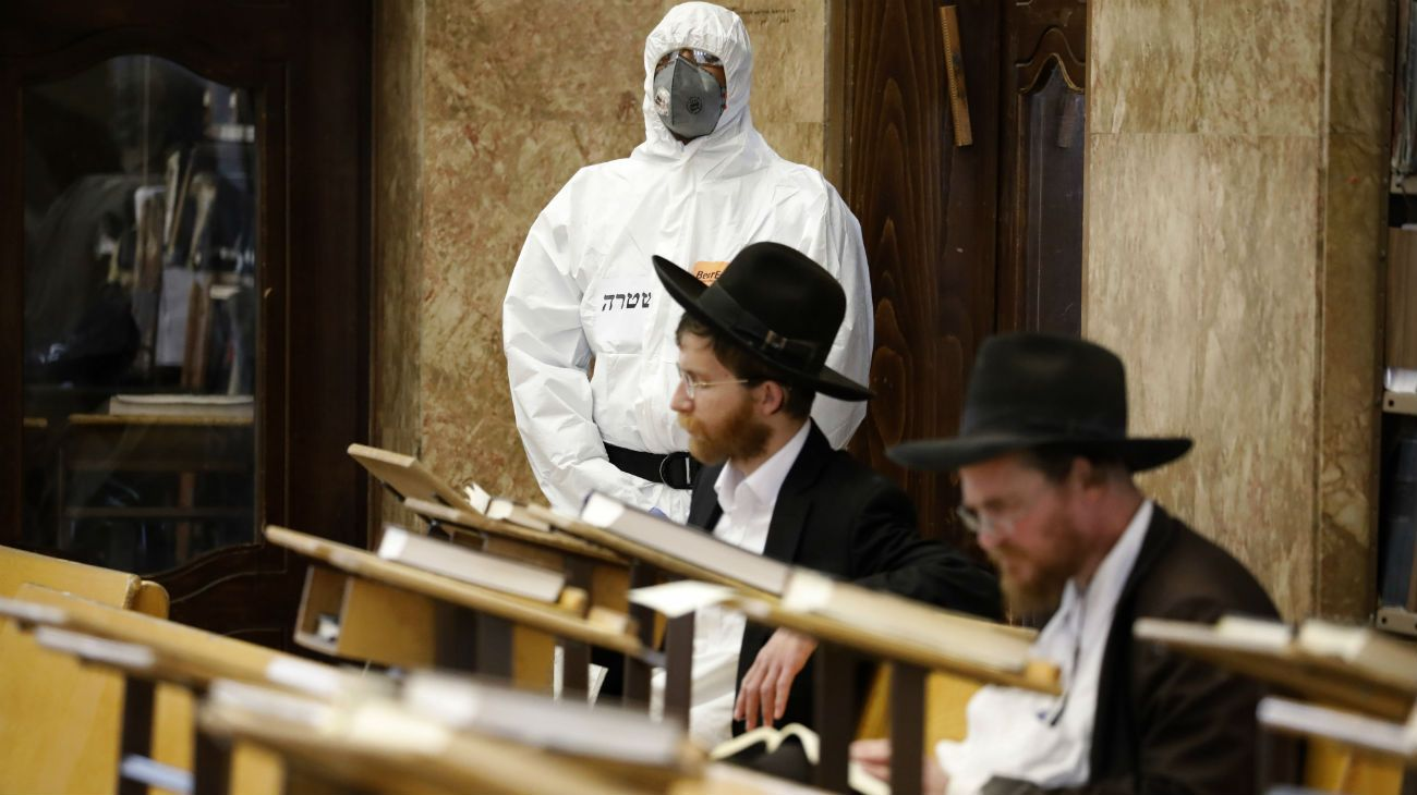 Un policía con protección a la pandemia espera que dos religiosos terminen de rezar en una sinagoga para detenerlos por violar las restricciones al coronavirus.