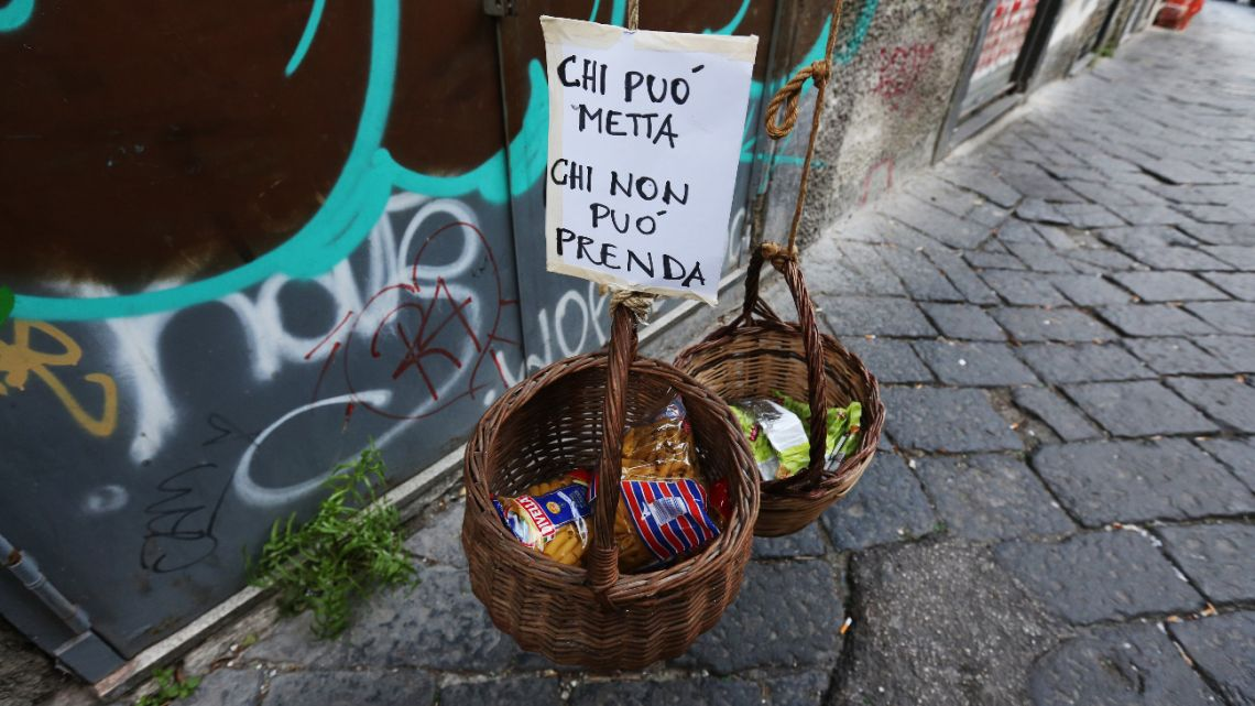 "This picture shows two solidarity baskets ('Panaro solidare') displayed with a note reading ""Who can put, who cannot take"" in one of the deserted streets in the historic center of Naples on April 3, 2020."