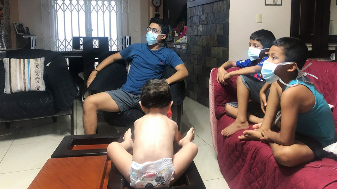 In this March 26, 2020, photo, relatives of Bella Lamilla – the first person to be diagnosed with coronavirus in Ecuador – maintain quarantine in their home in Babahoyo, Ecuador.