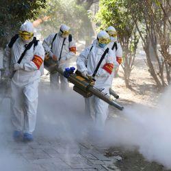 Miembros del equipo de la policía encargado de la sanidad inoculan spray desinfectante como medida preventiva ante la propagación del Coronaviros en la ciudad china de Bozhou.,
