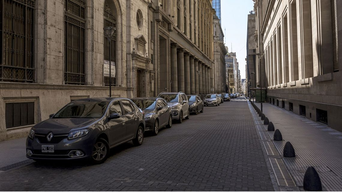 Vehicles sit parked along a near deserted road in the financial district of Buenos Aires.