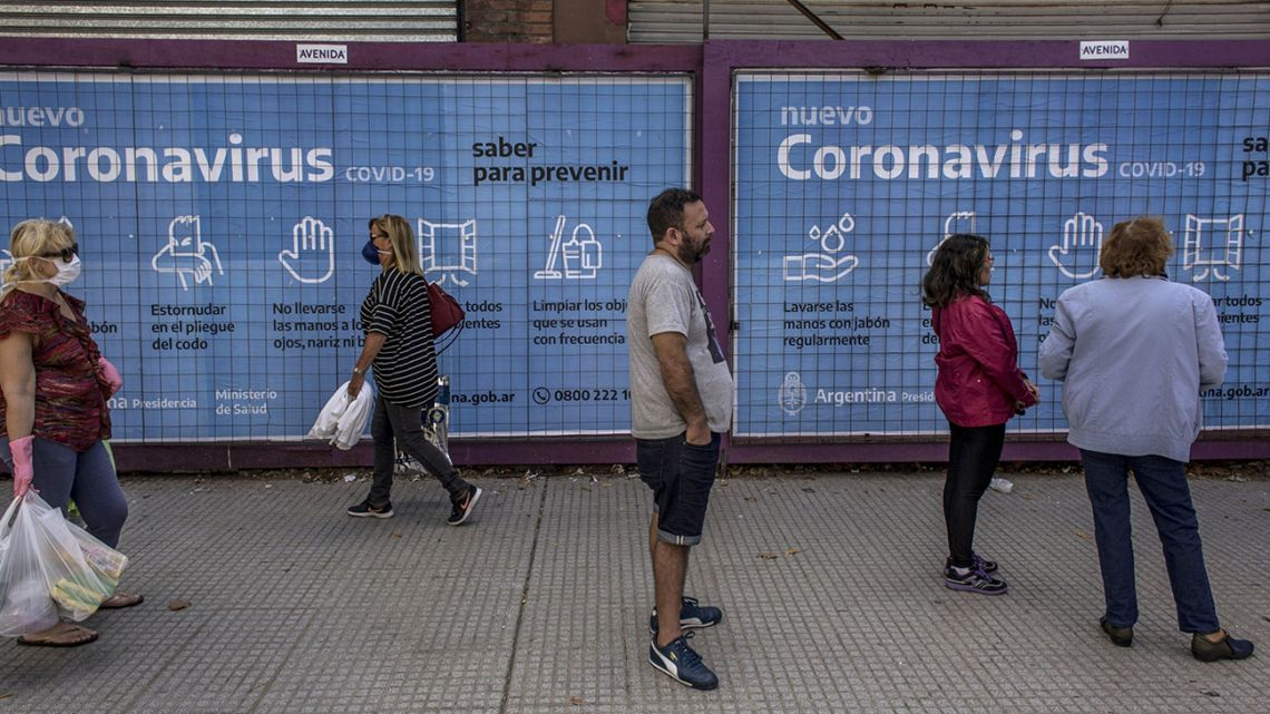 Porteños queue outside a bank in Buenos Aires, backdropped by state advertising about the coronavirus pandemic.