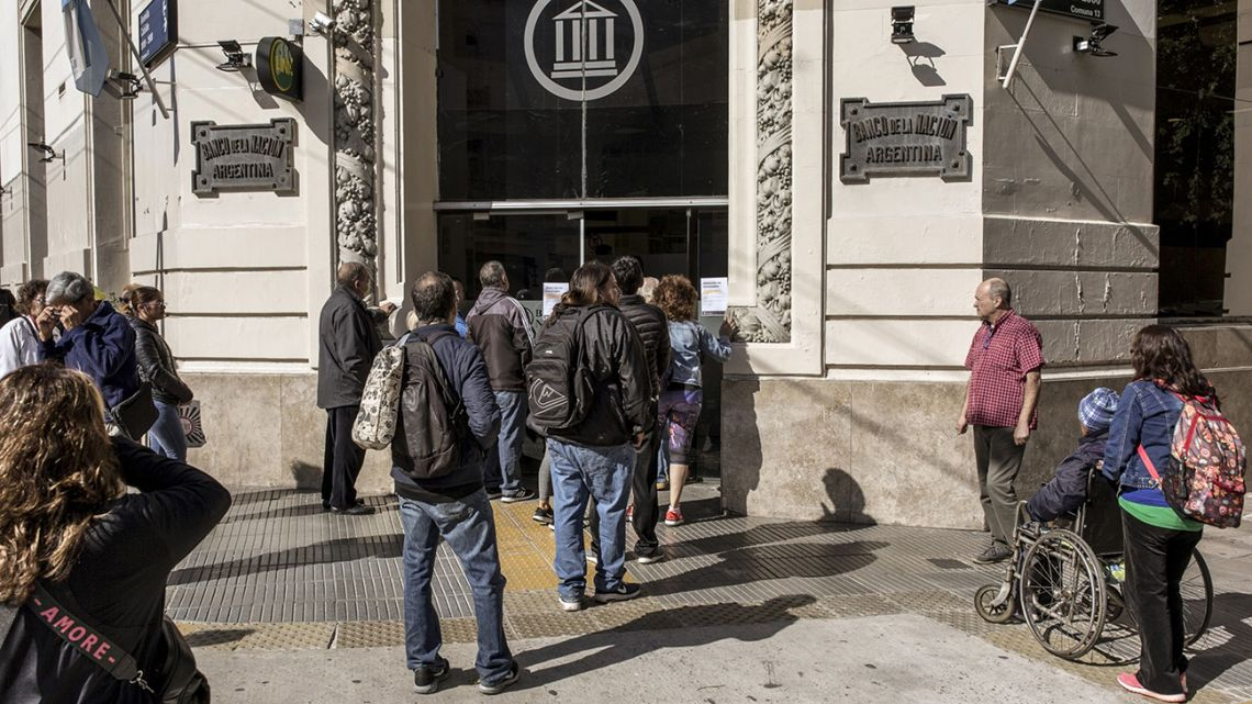 People line up in front of a branch of Banco de la Nación in Buenos Aires, during the coronavirus pandemic, on Friday, April 3, 2020.