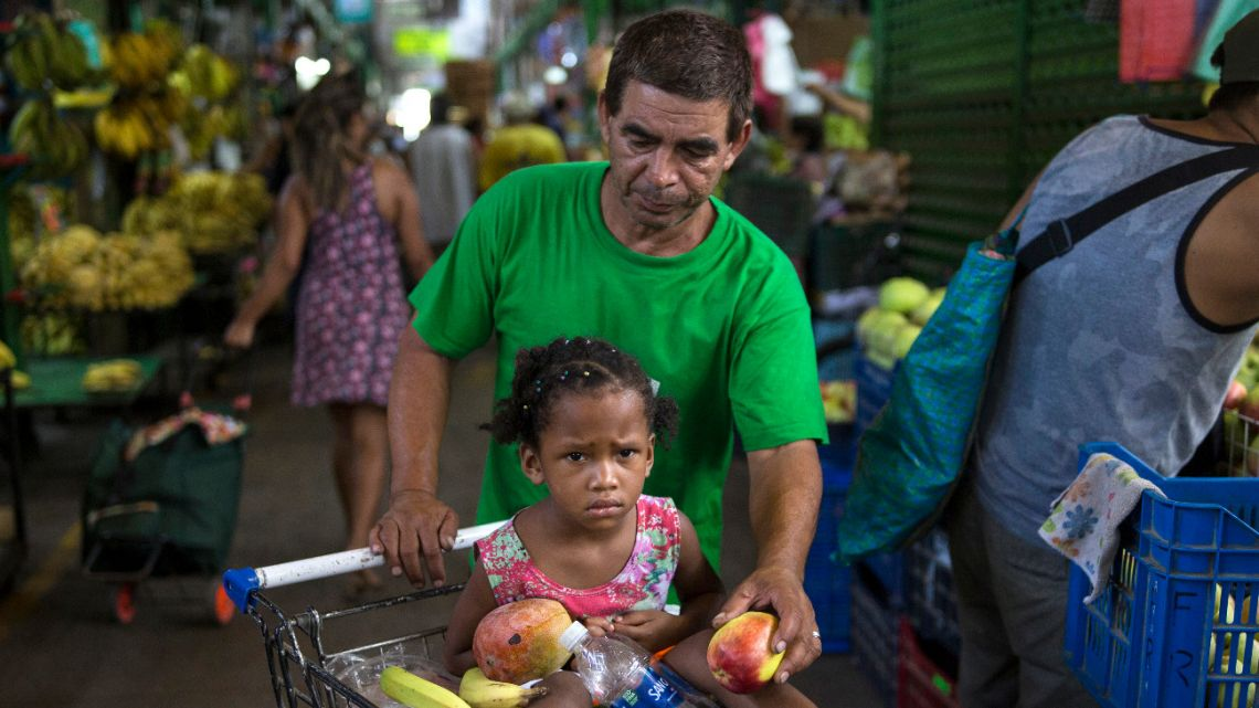 In this March 18, 2020 photo, Cesar Alegre, accompanied by his 4-year-old daughter Lia, places a damaged apple in his shopping cart filled with discarded produce given to him by vendors at a popular market in Lima, Peru.