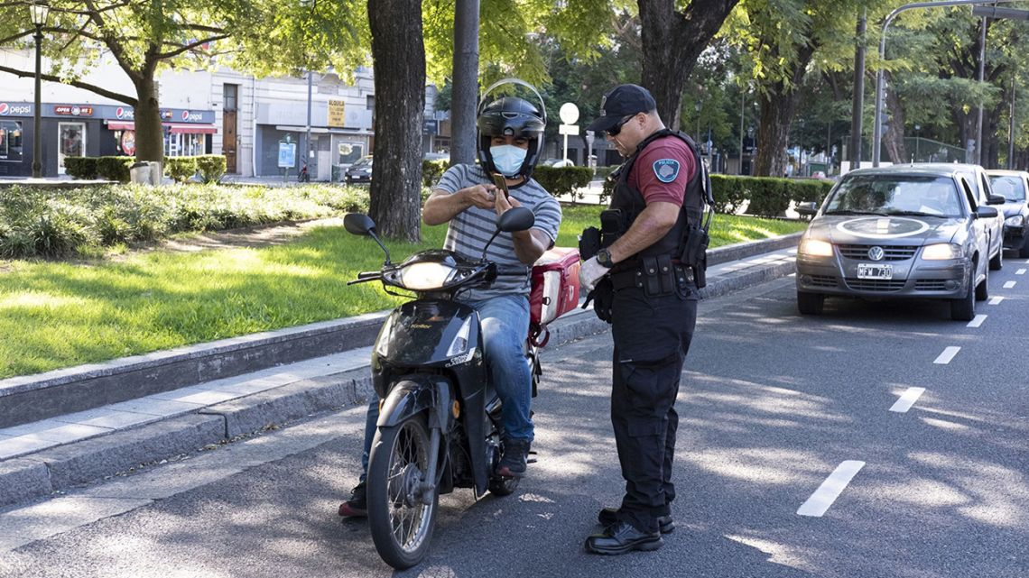 A police officer inspects a motorcyclist's credentials at a checkpoint on 9 de Julio Avenue in Buenos Aires.