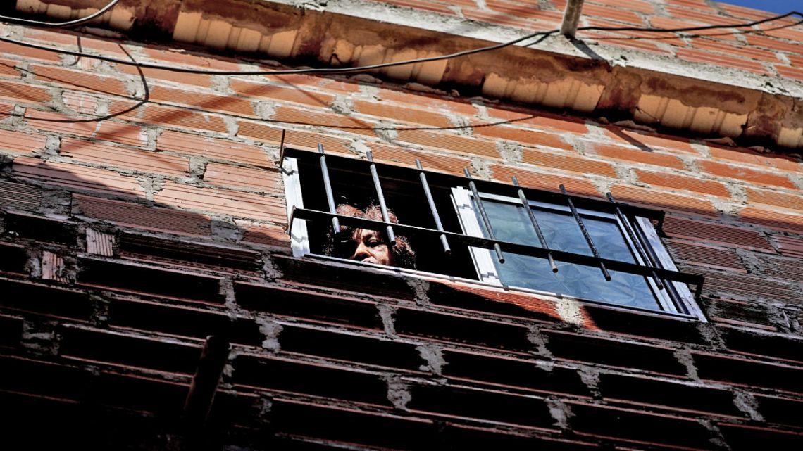 Woman looking through window during lockdown.