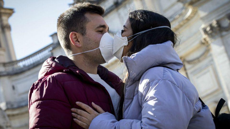 Italia: Una pareja se besa con sus barbijos puestos en los comienzos de la pandemia