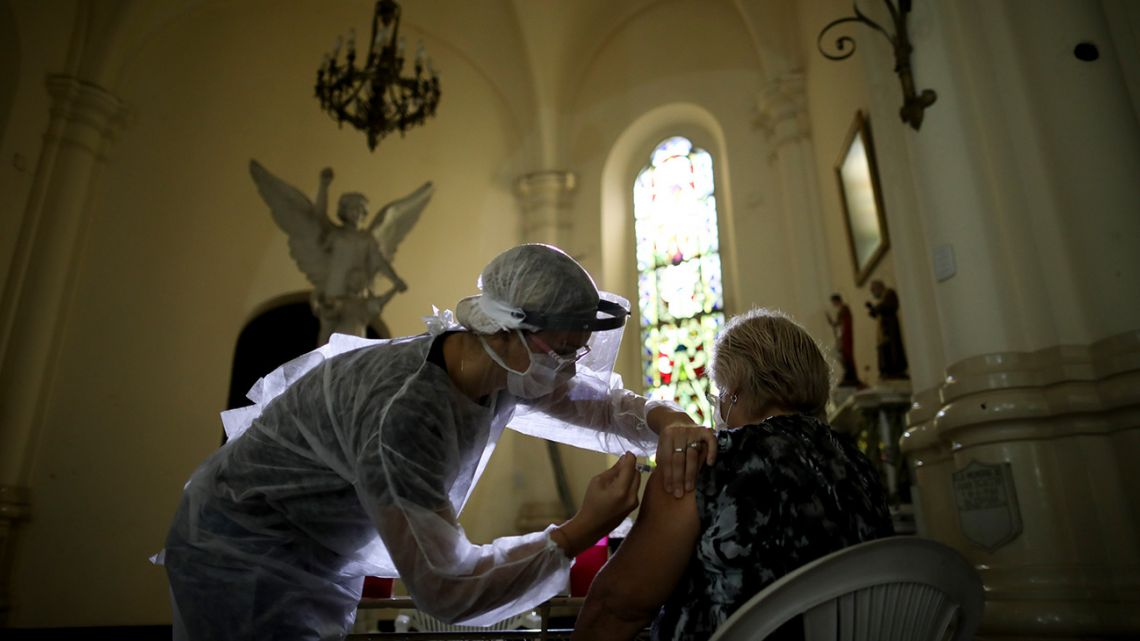 A medical worker injects an elderly woman with a flu vaccine inside a church as part of a government vaccination campaign, in Buenos Aires, Argentina, Saturday, April 11, 2020. Health authorities are encouraging people over 65 to be vaccinated against the flu, also a respiratory disease, to reduce complications of those who might contact Covid-19.