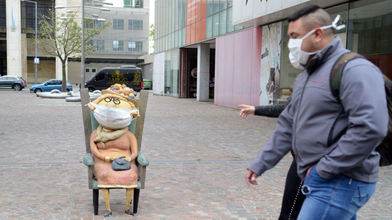 Estatuas y gente con barbijos an te la obligatoriedad del uso en la Ciudad de Buenos Aires