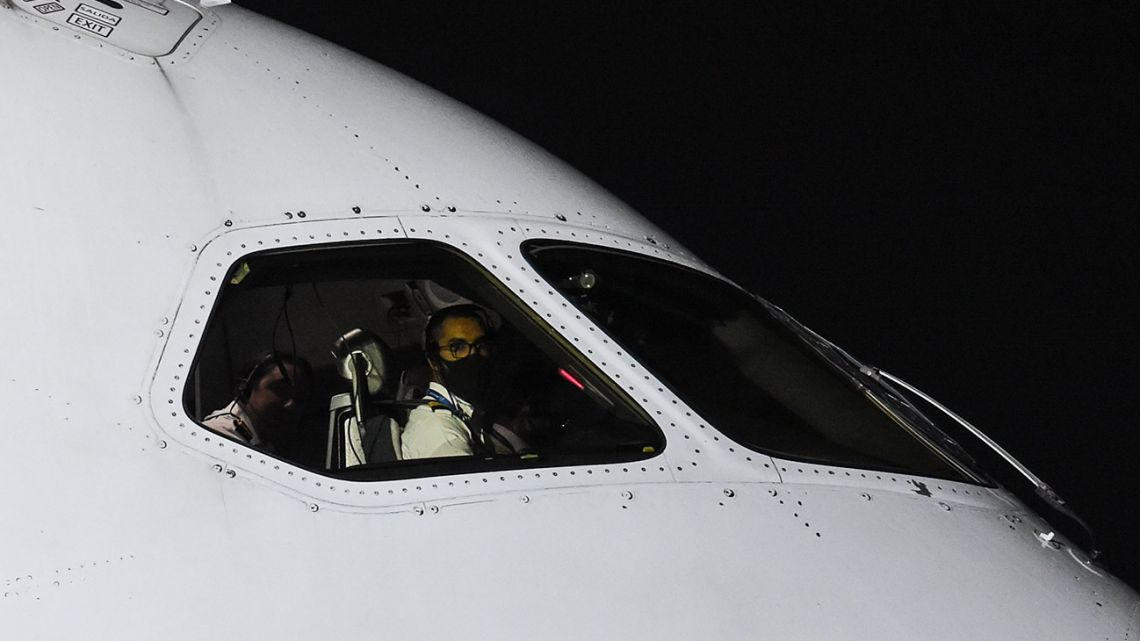 A pilot wears a face mask, while seated in a plane at an airport in Mexico City on April 7, 2020.