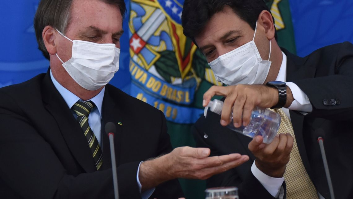 In this March 18, 2019 file photo, Brazil's Health Minister Luiz Henrique Mandetta, right, gives anti-bacterial gel to President Jair Bolsonaro as they give a press conference on the new coronavirus at Planalto presidential palace in Brasilia, Brazil.