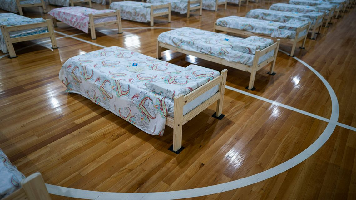 In this April 13, 2020, photo, cots, to be used by people infected with the new coronavirus, fill an indoor football court at the Argentine Football Association (AFA) training facility on the outskirts of Buenos Aires.