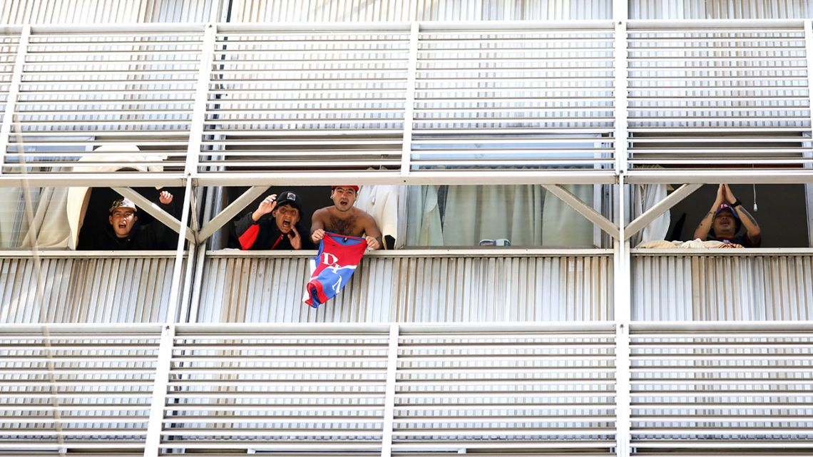 Fans of Independiente de Medellín shout to journalists from inside a hotel, in Buenos Aires, Argentina, Tuesday, April 14, 2020.