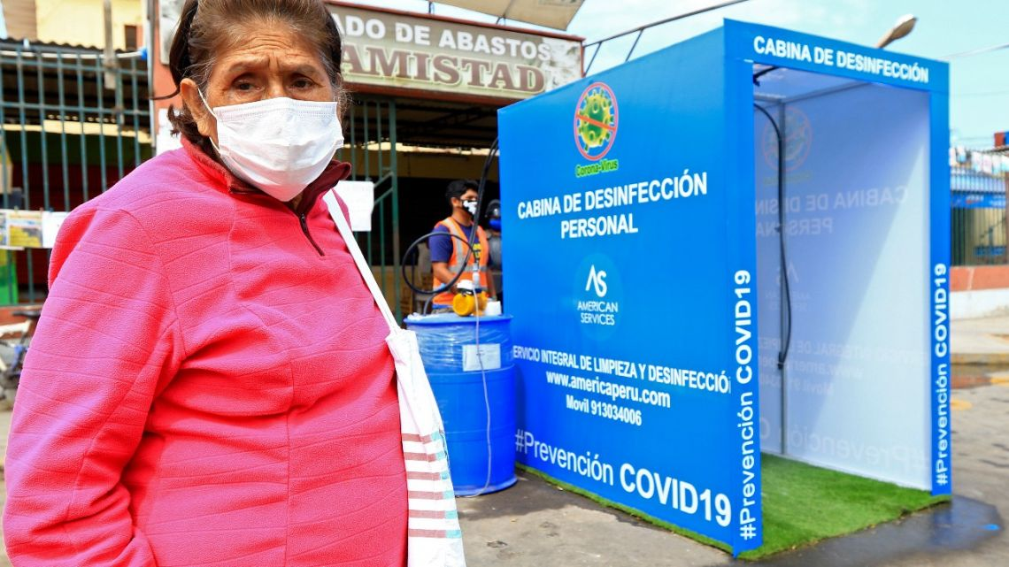 An elderly woman wearing a face mask prepares to enter a disinfection cabin against the spread of the new coronavirus placed at the entrance of La Amistad market in Moche, northern Peru, on April 14, 2020.