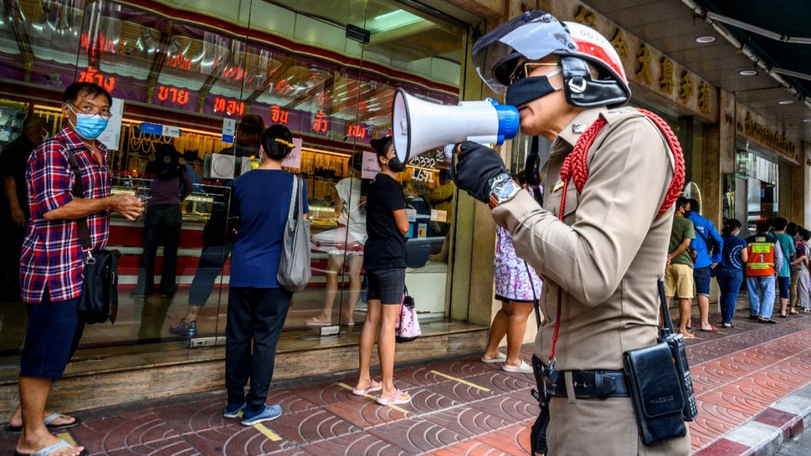 A police officer enforces social distancing as people wearing face masks amid fears of the spread of COVID-19 coronavirus line up to sell their jewelries in front of a gold shop in Bangkok's Chinatown on April 15, 2020.