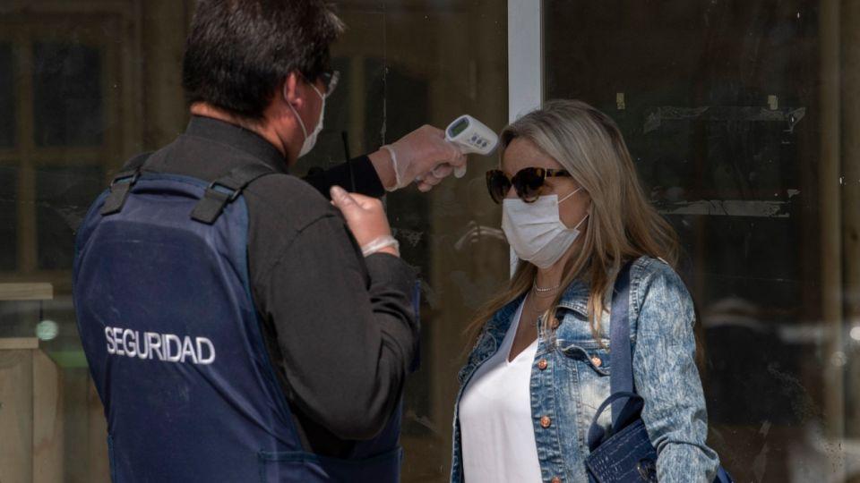 Un guardia de seguridad controla la temperatura a una ciudadana en Chile