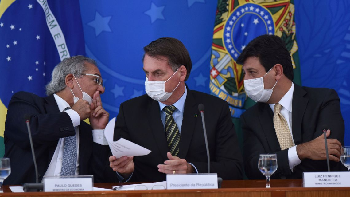 Brazil's President Jair Bolsonaro (center), along Economy Minister Paulo Guedes (left) who speaks to Health Minister Luiz Henrique Mandetta, during a press conference on the virus, at the Planalto Presidential Palace in Brasilia, on March 18, 2019.