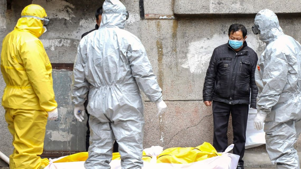In this February 1, 2020, file photo, funeral home workers remove the body of a person suspected to have died from the coronavirus outbreak from a residential building in Wuhan in central China's Hubei Province.
