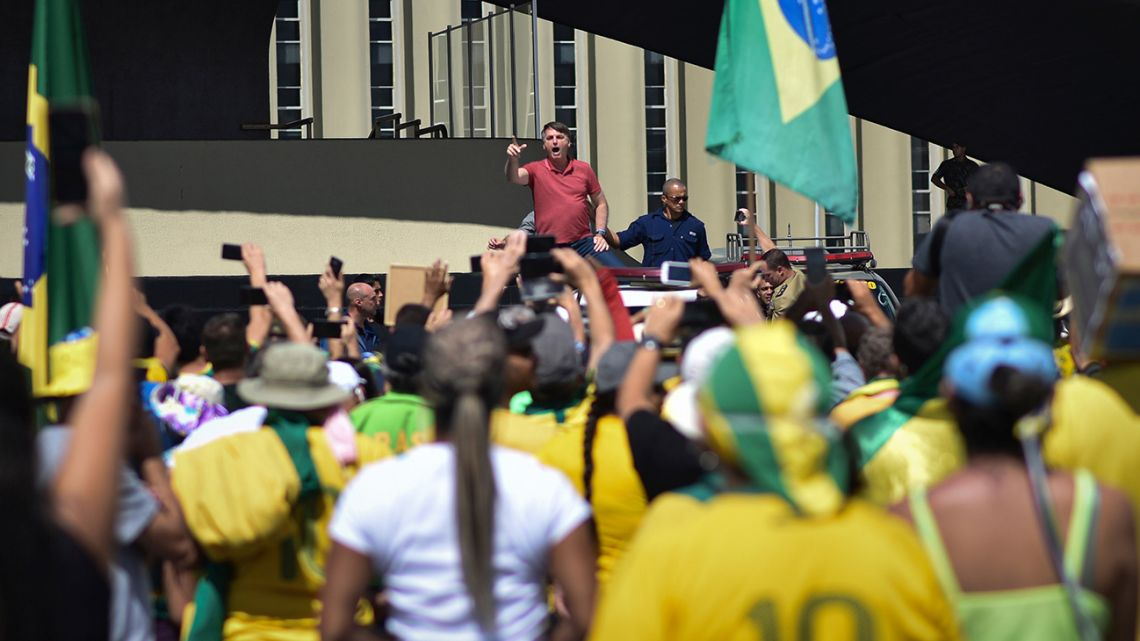 Brazil's President Jair Bolsonaro speaks to supporters during a protest in front the Army's headquarters during the Army day, amid the new coronavirus pandemic, in Brasilia, Brazil, Sunday, April 19, 2020.