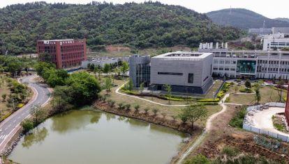 El laboratorio P4, de 3.000 m2, está localizado dentro de un edificio cuadrado con un anexo cilíndrico, cerca de un estanque, al pie de una colina boscosa, en las afueras de Wuhan.