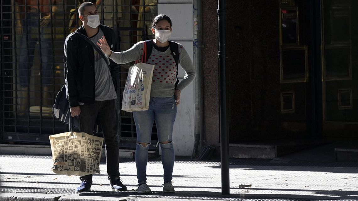 A couple wear face mask at a bus stop in Buenos Aires, on April 17, 2020, amid the Covid-19 coronavirus pandemic.