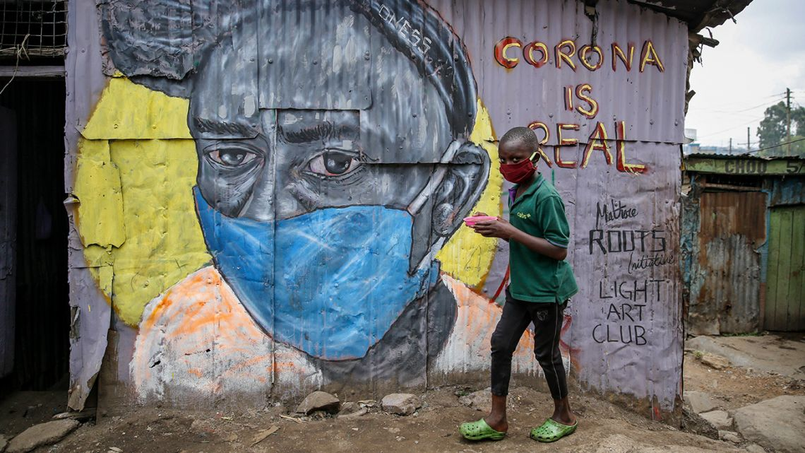 "A boy wearing a face mask carries a small bowl of ""githeri"", or mixed beans and maize, for him to eat as he walks past an informational mural warning people about the risk of the new coronavirus, painted by graffiti artists from the Mathare Roots youth group, in the Mathare slum, or informal settlement, of Nairobi, Kenya Saturday, April 18, 2020."