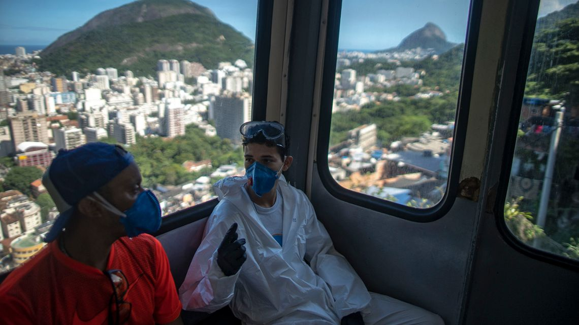 Volunteers disinfecting the Santa Marta favela in Rio de Janeiro, Brazil, during the Covid-19 coronavirus pandemic take the elevator on April 20, 2020.