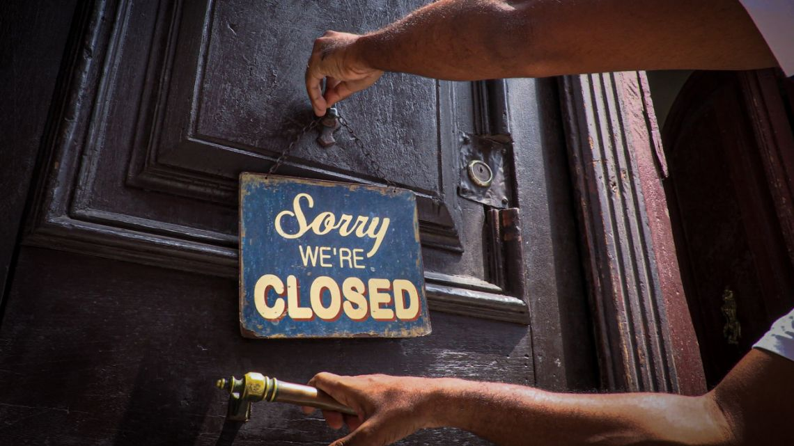 An employee hangs a sign outside the door of Nelson's Cafe in Havana on March 16, 2020, amid the new coronavirus pandemic.