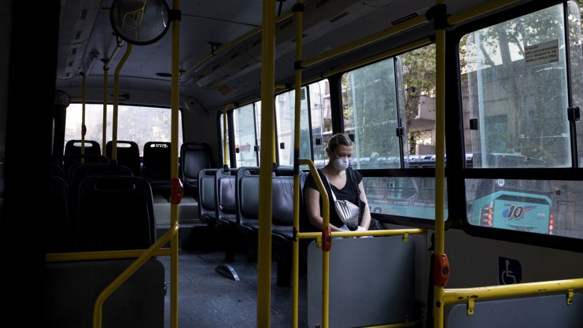 A passenger wearing a protective mask travels on an almost empty bus in Buenos Aires.