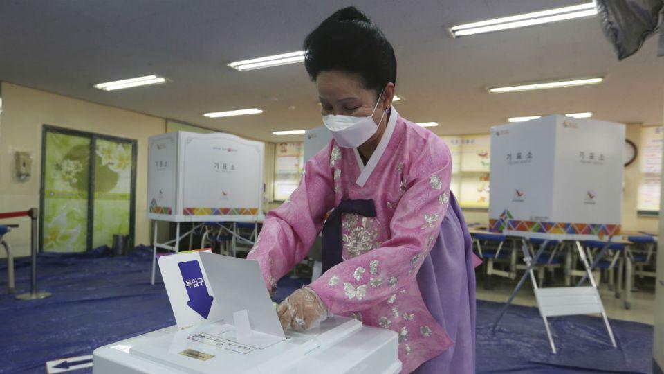 Una mujer con atuendo típico y protección al Covid-19 emite su voto en las elecciones de esta semana.