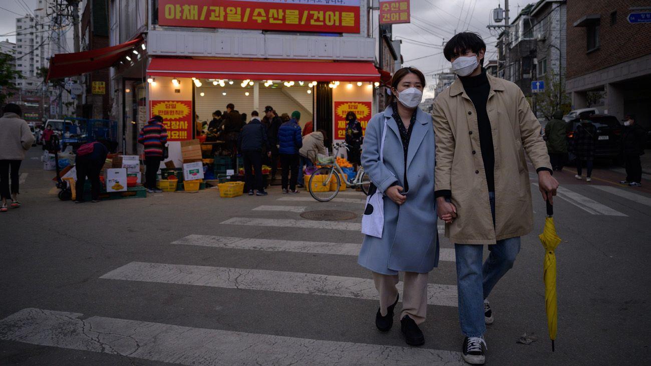 La gente usa barbijos y tapabocas en la calle y recorriendo un mercado de Seúl
