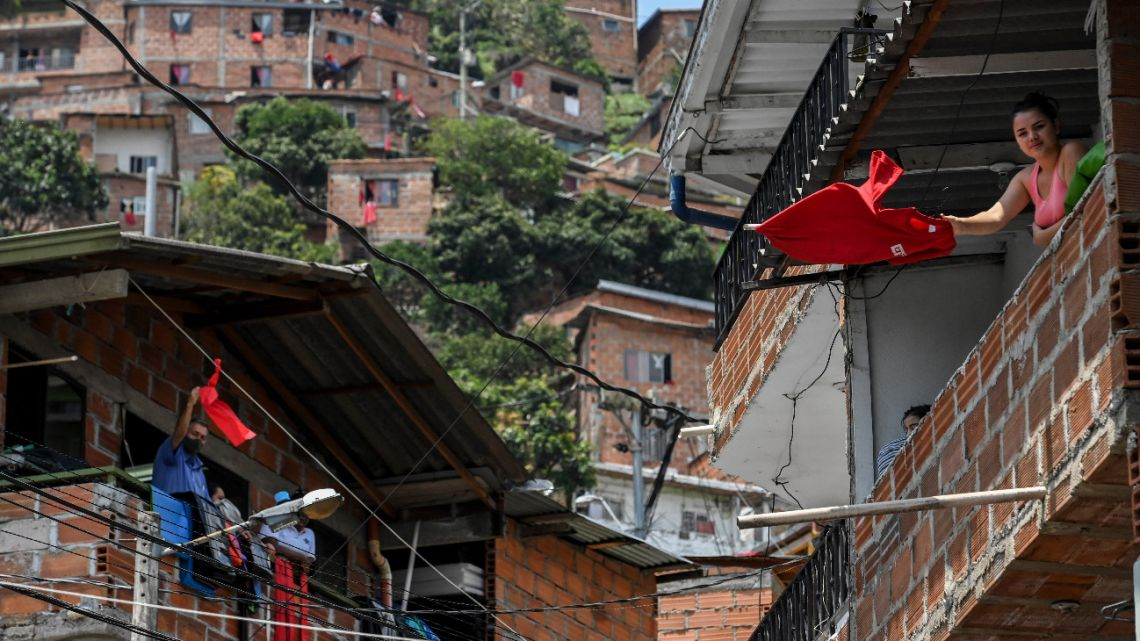 People wave red cloth as a distress signal to receive government aid amid the coronavirus (COVID-19) outbreak , at the Comuna 13 neighborhood in Medellin, Colombia on April 16, 2020.