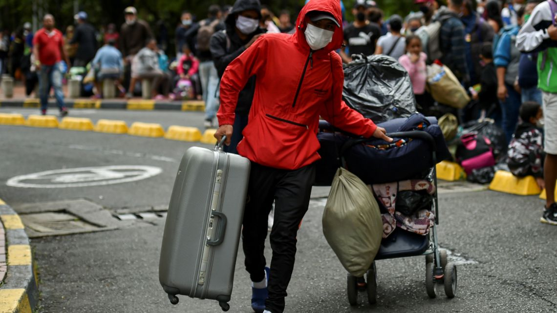 A Venezuelan migrant carries his luggage before boarding a bus to voluntarily return to their country because of the novel coronavirus COVID-19 pandemic, in Cali, Colombia, on April 14, 2020.