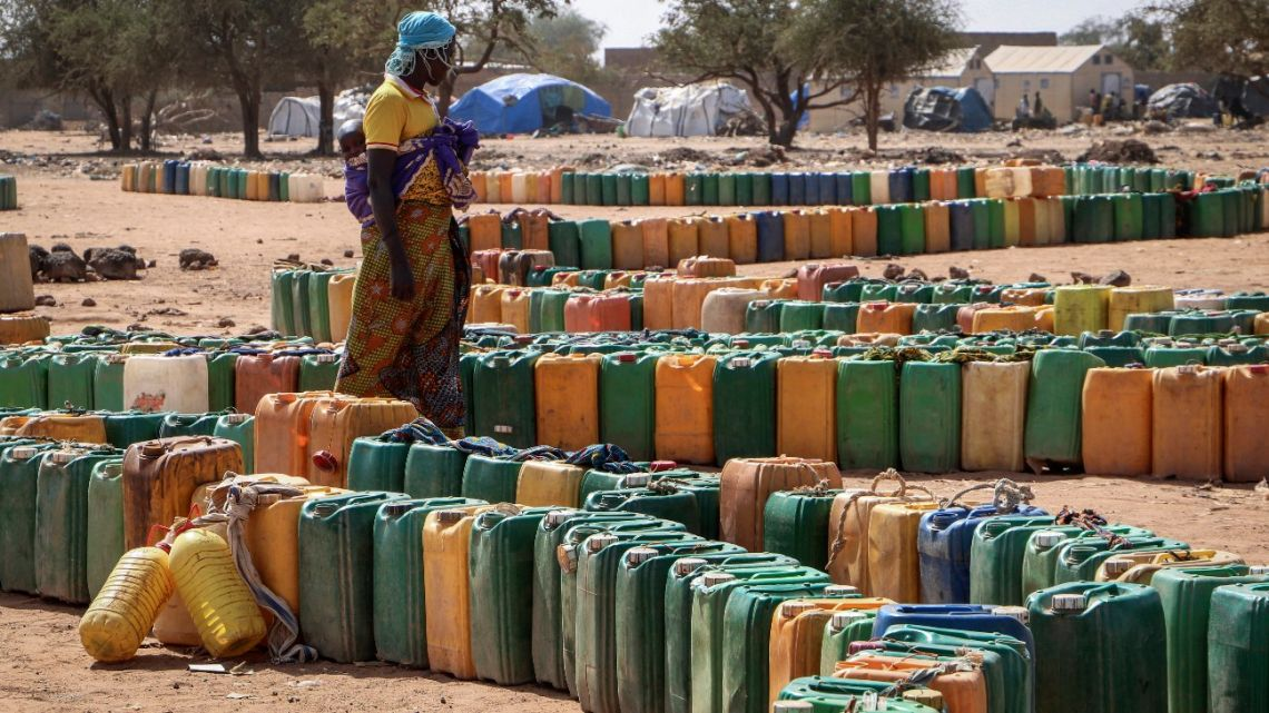 In this photo taken Monday, December 9, 2019, plastic containers belonging to displaced people sit queued up in lines, waiting their turn to be filled with water from a well, at a makeshift camp for the internally displaced in Barsalogho, in northern Burkina Faso.