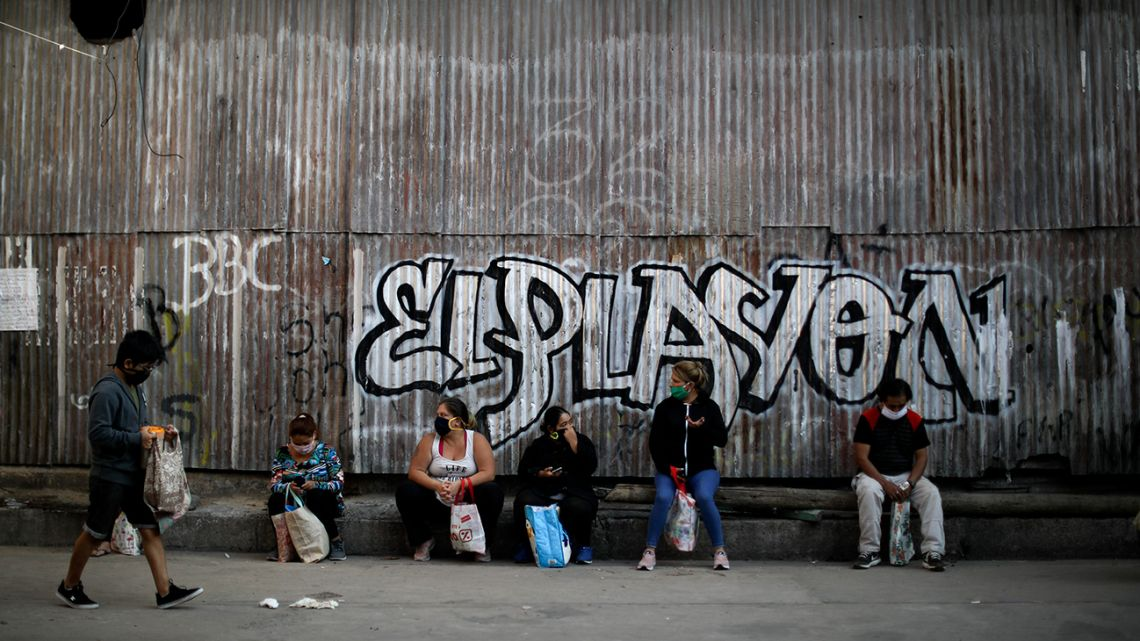 People sit outside a soup kitchen waiting their turn to receive free food for their families during a government-ordered lockdown to curb the spread of the new coronavirus, in Buenos Aires, Argentina, Tuesday, April 21, 2020.