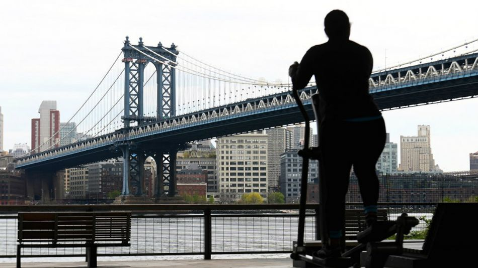 Solitaria, una personas ejercita este jueves 23 de abril en Nueva York, con el puente de Manhattan de fondo.