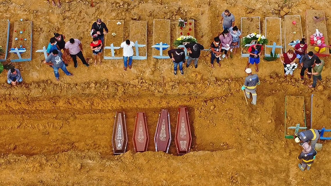 Aerial picture showing a burial taking place at an area where new graves have been dug up at the Nossa Senhora Aparecida cemetery in Manaus, in the Amazon forest in Brazil, on April 22, 2020.