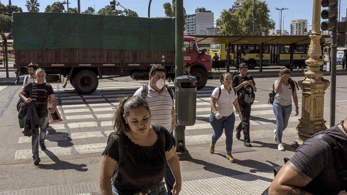 Porteños, some wearing face masks, cross a street in Buenos Aires.