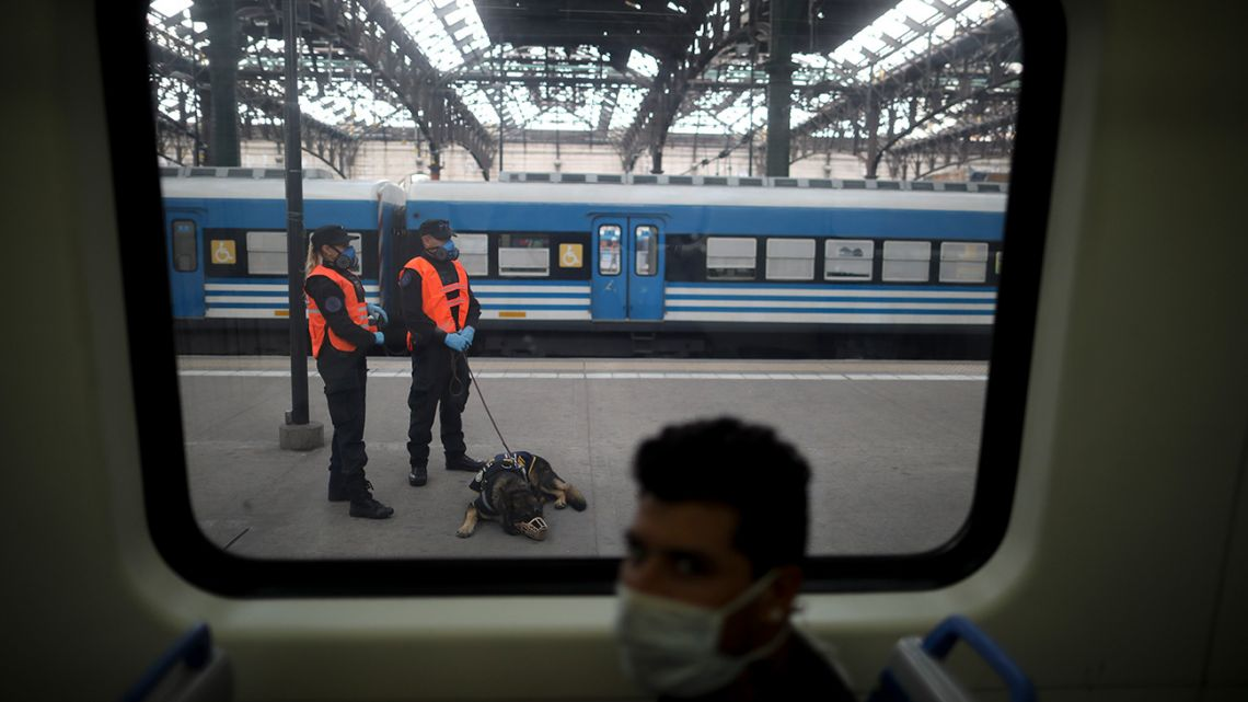 Police officers wearing face masks, pictured through the window of a train at Retiro station, during the coronavirus pandemic.