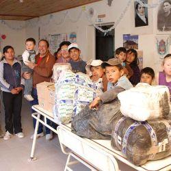 Los niños de Antofalla y su maestro sonríen junto a algunas donaciones de los caravaneros.