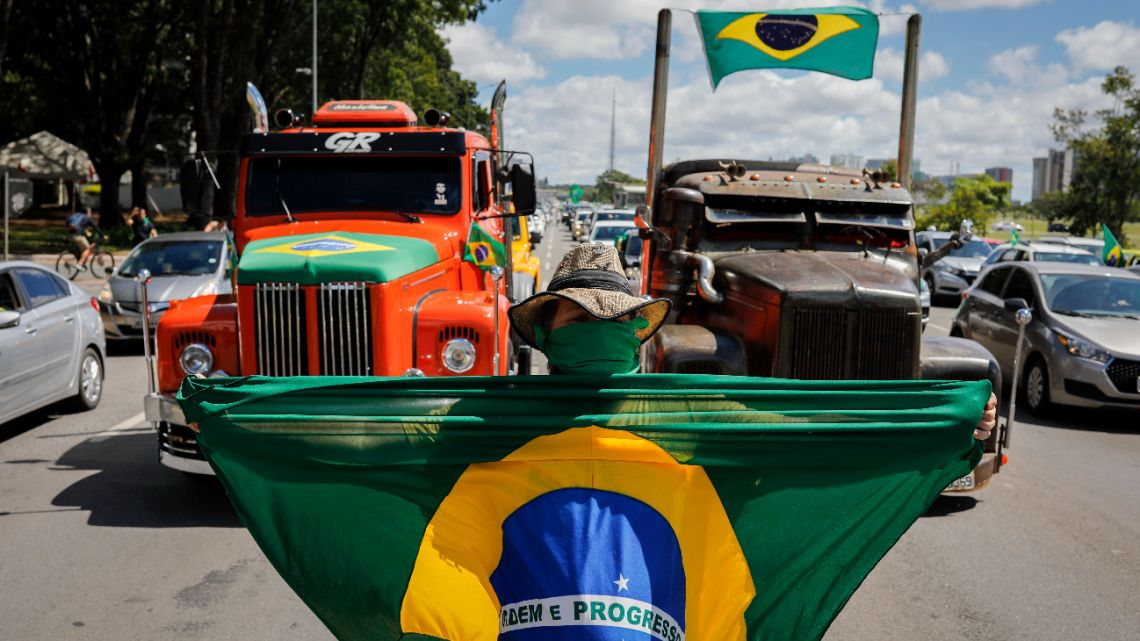 A supporter of anti-quarantine Brazilian President Jair Bolsonaro displays a Brazilian flag during a motorcade against the quarantine and social distance measures imposed to combat the novel coronavirus, in Brasilia on April 26, 2020.