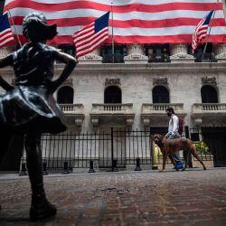 La estatua de Fearless Girl se ve frente a la Bolsa de Nueva York (NYSE) el 30 de abril de 2020 en la ciudad de Nueva York. - Las acciones de Wall Street abrieron a la baja el jueves luego de otro aumento de las solicitudes de desempleo a raíz de los cierres de coronavirus, compensando los fuertes resultados de los gigantes tecnológicos. Otros 3.84 millones de trabajadores estadounidenses solicitaron beneficios de desempleo la semana pasada y el total ahora ha superado los 30 millones en seis semanas, según datos del Departamento de Trabajo. (Foto de Johannes EISELE / AFP) | Foto:AFP