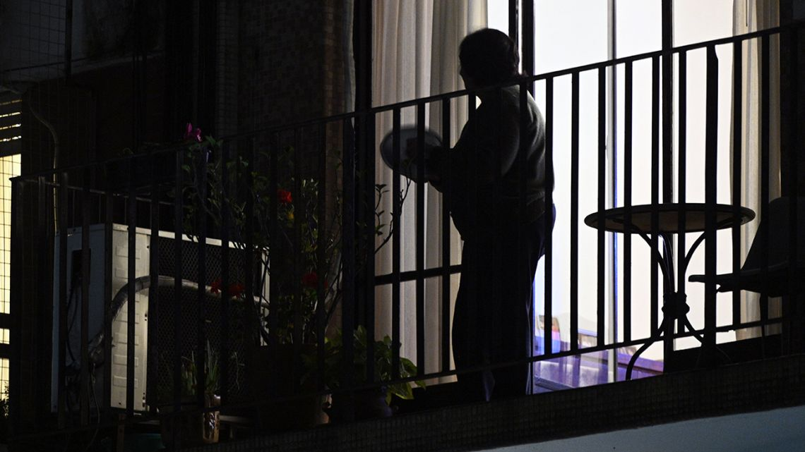 A woman bangs a pan from her balcony to protest against the liberation of inmates to prevent the spread of the new coronavirus in prisons, in Buenos Aires, on April 30, 2020.