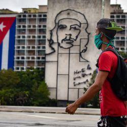 Un hombre camina frente al edificio del Ministerio del Interior con la imagen del legendario líder guerrillero Ernesto  | Foto:AFP